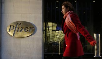 A woman passes Pfizer's world headquarters, Monday, Nov. 23, 2015, in New York. Pfizer and Allergan will join in a $160 billion deal to create the world's largest drugmaker. (AP Photo/Mark Lennihan)