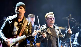 Bono, right, leader of Irish rock band U2, performs in Turin, Italy, in this Sept. 4, 2015, file photo. U2 has rescheduled two shows in Paris postponed after the Nov. 13 attacks in the city. The band had been due to play Paris Nov. 14 and 15; the new concerts were scheduled for Dec. 6 and 7. (Alessandro Di Marco/ANSA via AP, File)