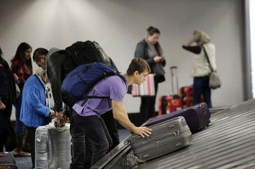 A traveler gathers his luggage at the San Francisco International Airport Sunday in San Francisco. (Associated Press)