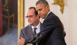 President Barack Obama and French President Francois Hollande embrace during a joint news conference in the East Room of the White House in Washington, Tuesday, Nov. 24, 2015. Hollande's visit to Washington is part of a diplomatic offensive to get the international community to bolster the campaign against the Islamic State militants. (AP Photo/Andrew Harnik)