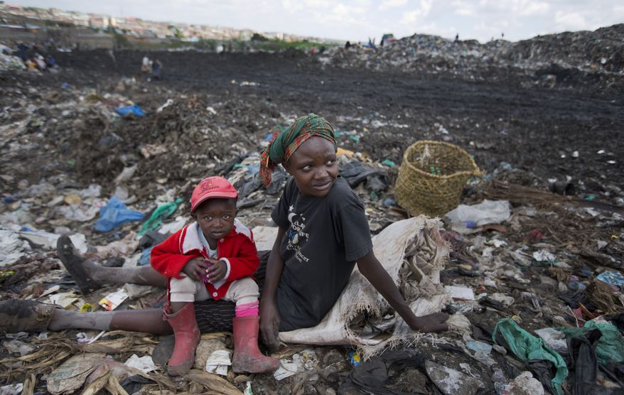 In this photo taken Thursday, Nov. 12, 2015, Agnes Njoki, 17, takes a break with her daughter, Shantel Akinyi, 2, who accompanies her as she works scavenging for plastic at the garbage dump in the Dandora slum of Nairobi, Kenya. Men, women and children traipse through the murky sludge that weaves through mountains of garbage in Nairobi's notorious Dandora dump, hunting for anything that can be recycled to earn themselves enough for their daily bread - some of the poorest of Kenya's poor and those likely to be on Pope Francis' mind when he makes his first trip to Africa this week and brings his message of environmental stewardship and care for society's most marginal. (AP Photo/Ben Curtis)