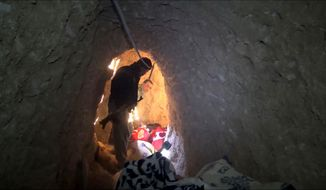 In this image made from video taken on Sunday, Nov. 22, 2015, Kurdish security forces are seen in a tunnel complex under the city of Sinjar, northern Iraq that were used by Islamic State fighters to move undetected and avoid coalition airstrikes before the town was retaken from the militants. (AP Photo via AP video)