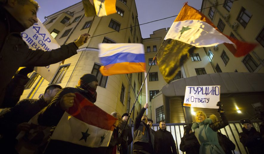 "A woman holds a poster reading ""Turkey to account!"" as others wave Russian and Syrian national flags during a picket at the Turkish Embassy in Moscow on Tuesday, Nov. 24, 2015. Russian President Vladimir Putin called Turkey's decision to down a Russian jet near the Syria border a ""stab in the back."" (Associated Press)"