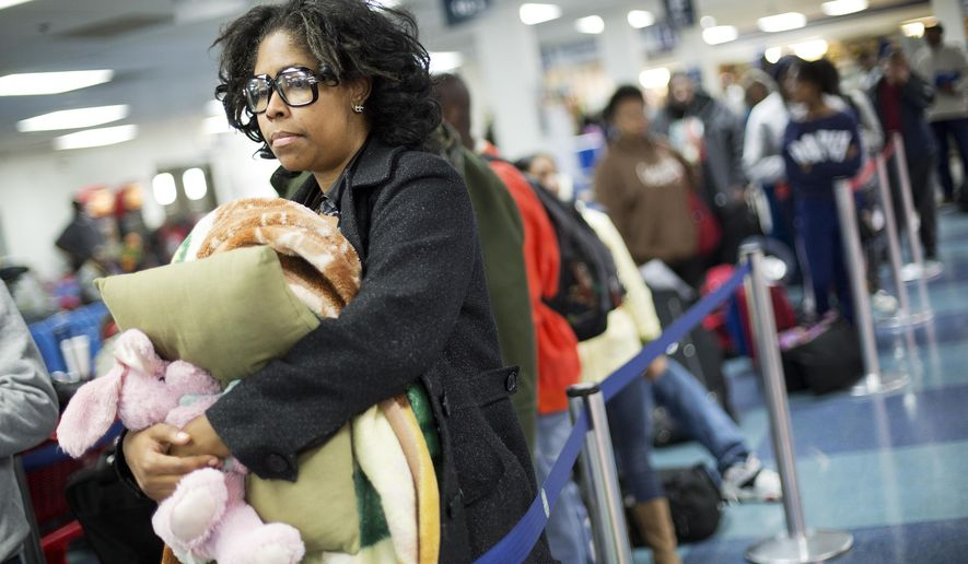Valarie Settle, of Roanoke Va., waits in line at a Greyhound station to board a bus as she heads to California for the Thanksgiving holiday Tuesday, Nov. 24, 2015, in Atlanta. An estimated 46.9 million Americans are expected to take a car, plane, bus or train at least 50 miles from home over the long holiday weekend, according to the motoring organization AAA. That would be an increase of more than 300,000 people over last year, and the most travelers since 2007. (AP Photo/David Goldman)
