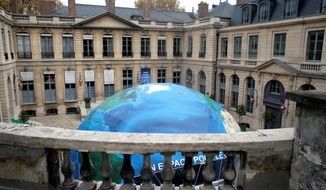An globelike tent hosting an exhibition on climate is set up in the courtyard of the French Environment Ministry. President Obama will head to a historic climate change summit in Paris next week. (Associated Press)