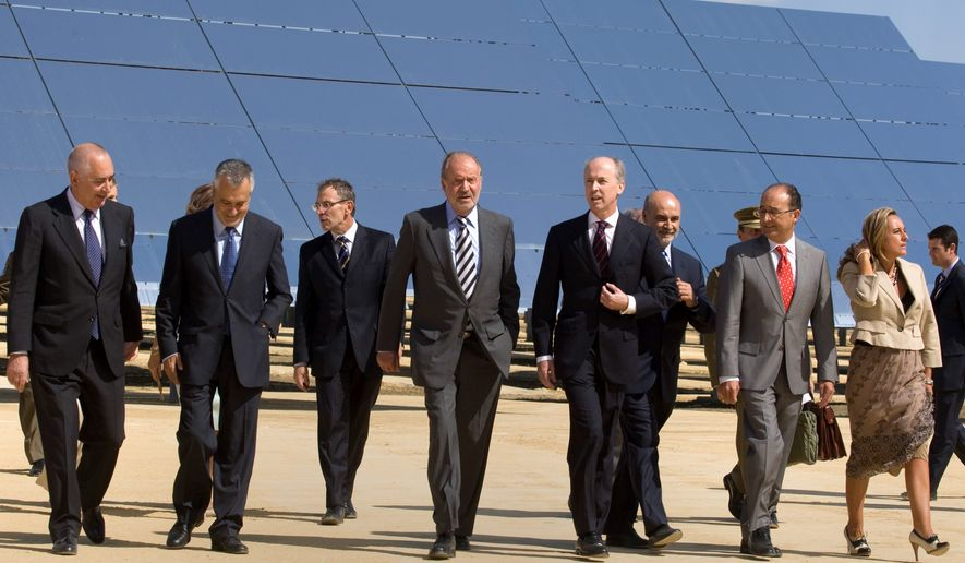 Spain's King Juan Carlos (fourth from left) walks with Abengoa Chairman Felipe Benjumea in front of solar panels during the inauguration of a solar tower in southern Spain. The firm, which is also constructing large-scale solar power projects in the U.S. and has received at least $2.7 billion in federal loan guarantees since 2010, said Wednesday it will begin insolvency proceedings. (Associated Press)