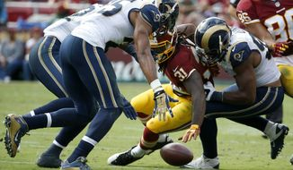 St. Louis Rams defense surrounds Washington Redskins running back Matt Jones (31) as he reaches for a loose ball during the second half of an NFL football game in Landover, Md., Sunday, Sept. 20, 2015. (AP Photo/Alex Brandon)