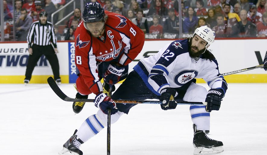 Washington Capitals left wing Alex Ovechkin (8), from Russia, goes airborne over the leg of Winnipeg Jets right wing Chris Thorburn (22) during the first period of an NHL hockey game, Wednesday, Nov. 25, 2015, in Washington. (AP Photo/Alex Brandon)