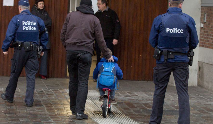 A man wheels a boy on his bicycle past police officers as they arrive for school in the center of Brussels on Wednesday, Nov. 25, 2015. Students in Brussels have begun returning to class after a citywide shutdown over fears that a series of simultaneous attacks could be launched around the Belgian capital. (AP Photo/Virginia Mayo)