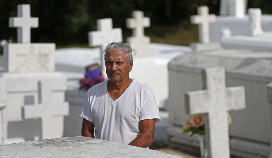 In this Oct. 30, 2015 photo, Giovanni R. Santini, appears at his wife's grave at a cemetery in Lafitte, La. Santini has spent decades trying to prove he's an American Indian, and folks in his bayou town no longer doubt he's a proud member of the 17,000-strong tribe Houma scattered across south Louisiana. Not so for the federal government. For decades, efforts by the Houma to become a federally recognized native American tribe have failed -- much like those of dozens of other groups nationwide. (AP Photo/Gerald Herbert)