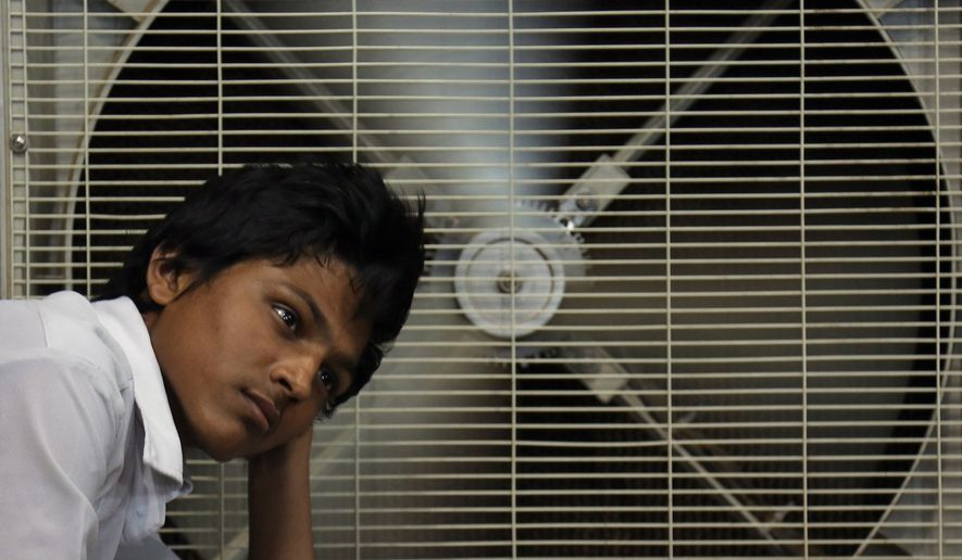 An Indian man rests in front of an air cooler to cool himself on a hot summer day in Hyderabad, in the southern Indian state of Telangana, in this May 31, 2015, file photo. (AP Photo/Mahesh Kumar A., File)