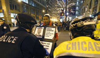 Dontreal Widow holds up a poster with the photo of  17 year-old Laquan McDonald and taunts Chicago police officers Wednesday, Nov. 25, 2015, one day after murder charges were brought against police officer Jason Van Dyke in the killing of McDonald, in Chicago. (AP Photo/Charles Rex Arbogast)