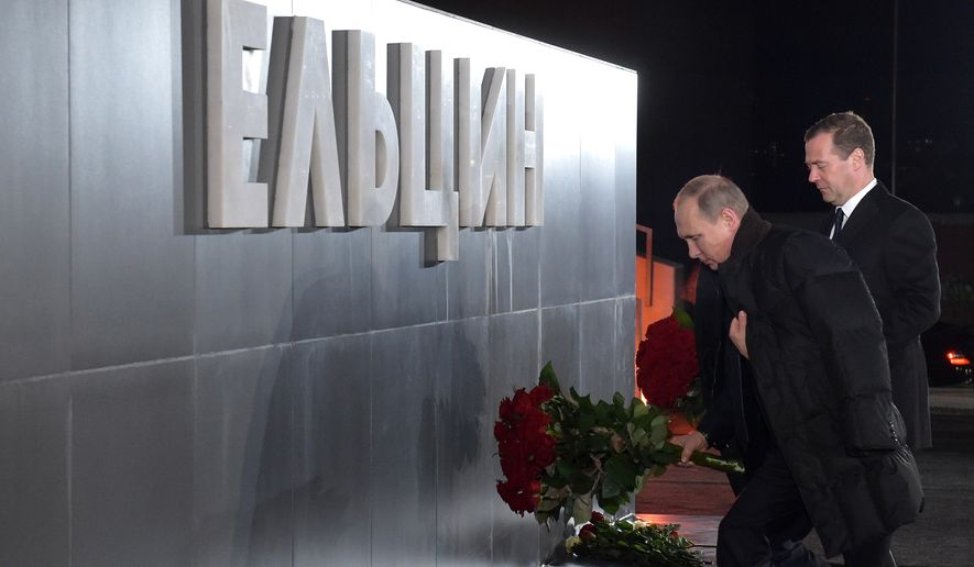 Russian President Vladimir Putin, left, and Prime Minister Dmitry Medvedev lay flowers at the monument to the first Russian President Boris Yeltsin in Yekaterinburg, the city in the Ural mountains, Russia, Wednesday, Nov. 25, 2015. The sign reads Yeltsin. (Alexander Astafyev/Sputnik, Government Pool Photo via AP)