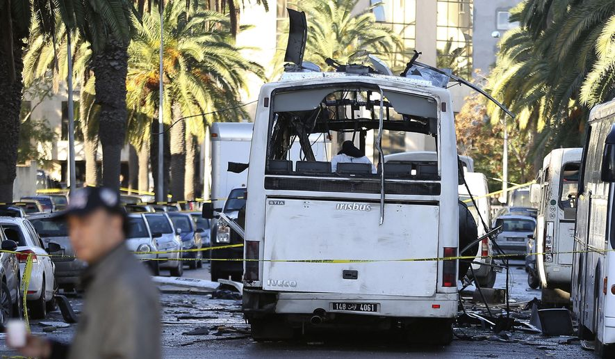 A man walks past the bus that exploded Tuesday in Tunis, Wednesday Nov.25, 2015.  Tunisia's president declared a 30-day state of emergency across the country and imposed an overnight curfew for the capital Tuesday after an explosion struck a bus carrying members of the presidential guard, killing at least 12 people and wounding 20 others. (AP Photo)