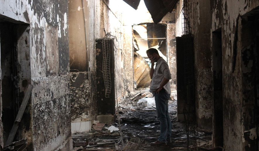FILE - In this Friday, Oct. 16, 2015, file photo, an employee of Doctors Without Borders walks inside the charred remains of their hospital after it was hit by a U.S. airstrike in Kunduz, Afghanistan. An investigative report on the U.S. air attack that killed more than two dozen civilians at a medical charity's hospital in northern Afghanistan last month says the crew of the attacking plane misidentified the target, believing it to be a government compound taken over by the Taliban.  (Najim Rahim via AP)