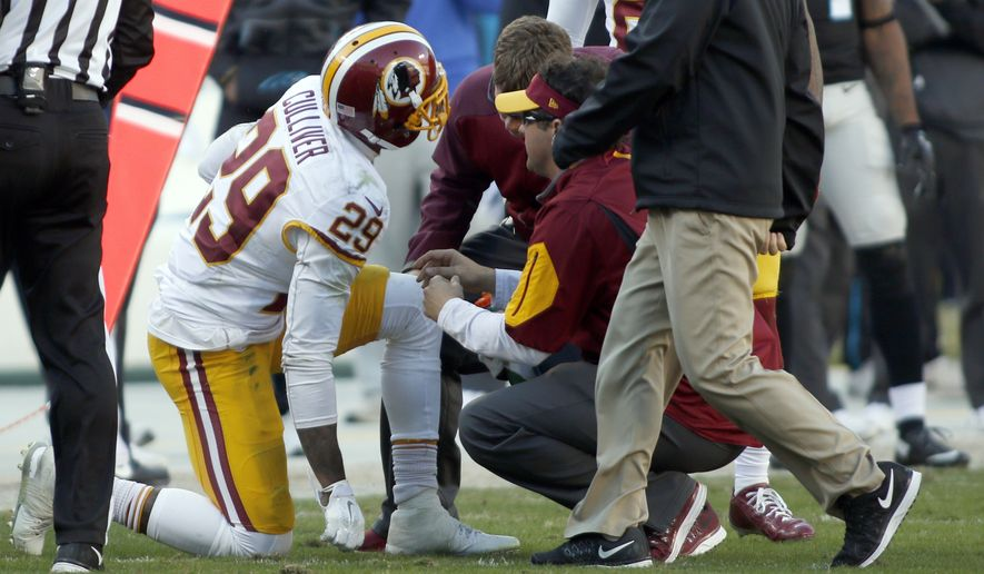 Team members attend to Washington Redskins' Chris Culliver (29) in the second half of an NFL football game against the Carolina Panthers in Charlotte, N.C., Sunday, Nov. 22, 2015. (AP Photo/Bob Leverone)