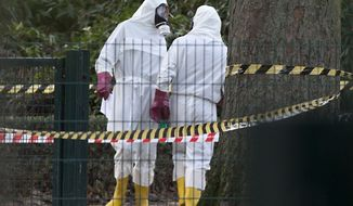Two men in white hazmat suits stand at the entrance of the Grand Mosque of Brussels on Thursday, Nov 26, 2015. Emergency personnel responded at the mosque after a suspicious package was found. (AP Photo/Virginia Mayo)