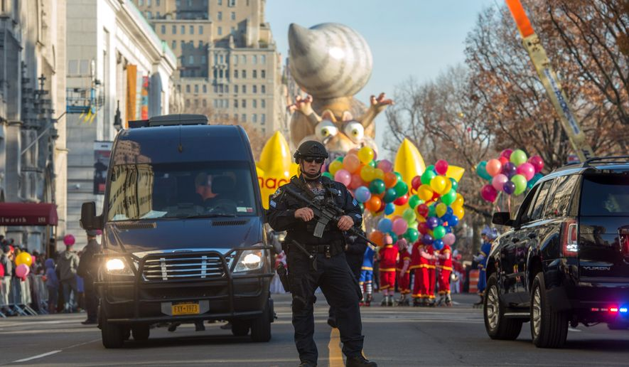 An armed police officer stands guard at the start of the Macy's Thanksgiving Day Parade, Thursday Nov. 26, 2015, in New York.  (AP Photo/Bryan R. Smith)