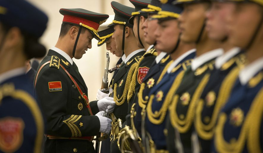 A Chinese honor guard member adjusts a fellow member's uniform before a welcome ceremony for the Czech Republic's Prime Minister Bohuslav Sobotka at the Great Hall of the People in Beijing, Friday, Nov. 27, 2015. In an effort to boost economic ties and influence in the region, China's top leaders met with leaders from central and eastern European countries in Beijing this week. (AP Photo/Mark Schiefelbein)