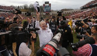 Virginia Tech head coach Frank Beamer is surrounded by media as he celebrates defeating Virginia 23-20 an NCAA college football game in Charlottesville, Va., Saturday, Nov. 28, 2015. (AP Photo/Steve Helber)