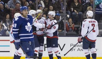 Washington Capitals' Tom Wilson, center, celebrates with teammates after scoring his team's second goal against the Toronto Maple Leafs as the Leafs' Joffrey Lupul, left, skates past during the second period of an NHL hockey game in Toronto, Saturday, Nov. 28, 2015. (Chris Young/The Canadian Press via AP) MANDATORY CREDIT