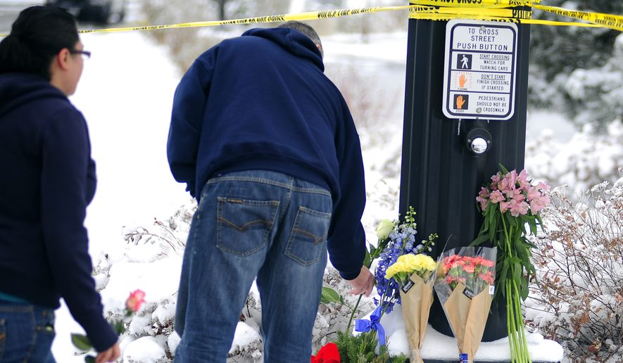 Colorado Springs residents Paul Nice and Denise Anchondo lay flowers Saturday in honor of the victims of Friday's deadly shooting at a Planned Parenthood clinic in Colorado Springs. (The Gazette via Associated Press)