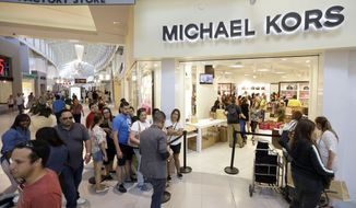 Shoppers line up outside a Michael Kors store at Dolphin Mall, Saturday, Nov. 28, 2015, in Miami. Store retailers saw fewer customer visits on Thanksgiving and Black Friday, compared with last year, according to Kevin Kearns, ShopperTrak's chief revenue officer. (AP Photo/Alan Diaz)