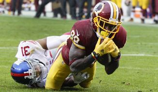 New York Giants defensive back Trevin Wade (31) stops Washington Redskins wide receiver Jamison Crowder (80) short of the goal line during the first half of an NFL football game in Landover, Md., Sunday, Nov. 29, 2015. (AP Photo/Mark Tenally)