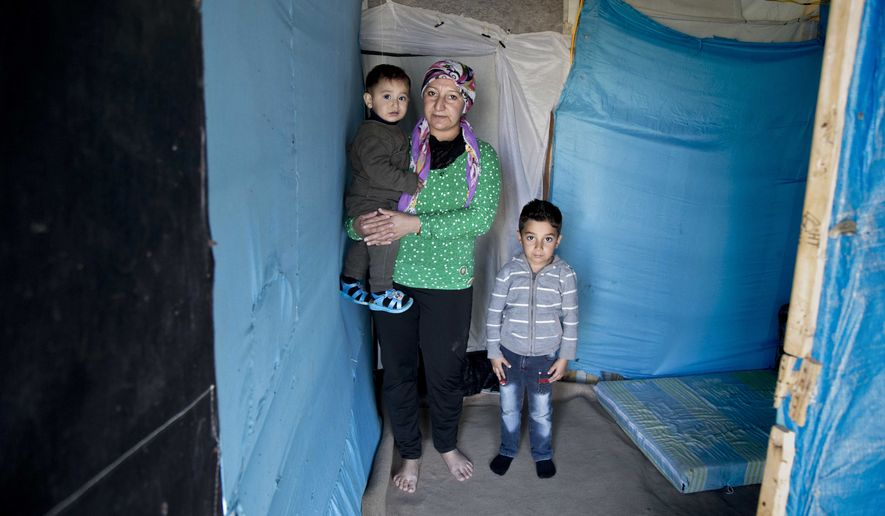 In this Saturday, Nov. 28, 2015 photo, Syrian refugee Yasra Mohammad poses for a photograph with her children, at an informal tented settlement, in Irbil, northern Iraq. Some 240,000 refugees who fled the fighting in Syria now live in Iraq. Their children are neither citizens of Syria, their families' country of origin, or of Iraq, the country where they now live. (AP Photo/Seivan M. Salim)