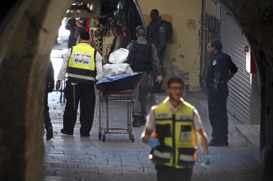An emergency service member stands next to the body of a Palestinian in Jerusalem's Old City, Sunday, Nov. 29, 2015. A Palestinian stabbed an Israeli police officer in Jerusalem on Sunday before being shot dead by security forces, police said. (AP Photo/Mahmoud Illean)