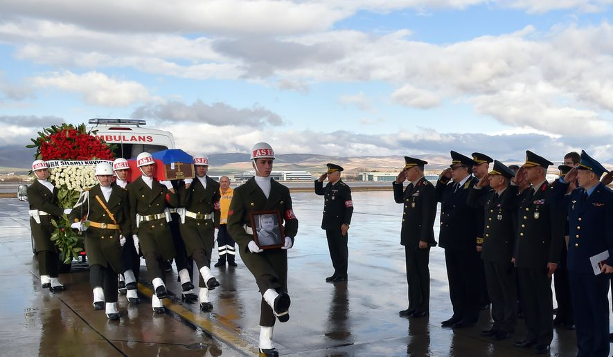 Turkish and Russian military officers salute as a Turkish honour guard carry the coffin of Russian pilot Lt. Col. Oleg Peshkov into a Russian Air Force transport plane at Esenboga Airport in Ankara, Turkey, Monday, Nov. 30, 2015. Early Saturday, Turkey had taken delivery of the body of Lt. Col Peshkov who was killed after Turkish F-16s shot down a Russian warplane near the Syrian-Turkish border last Tuesday. (Turkish Military, via AP)