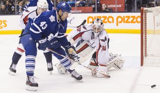 Washington Capitals' goalie Braden Holtby (70) makes a save in front of Toronto Maple Leafs' Nazem Kadri (43) during the second period of an NHL hockey game in Toronto, Saturday, Nov. 28, 2015. (Chris Young/The Canadian Press via AP)