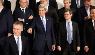 U.S. Secretary of State John Kerry, 2nd left, gestures as foreign ministers gather for a group photo at NATO headquarters in Brussels on Tuesday, Dec. 1, 2015. The NATO summit will take place in Warsaw in July 2016. (Jonathan Ernst/Pool via AP)