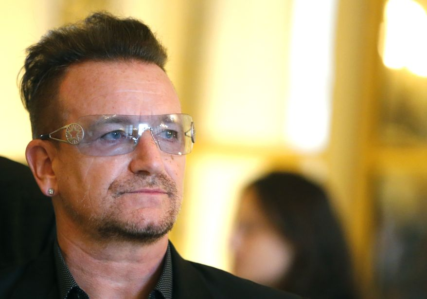"""This July 16, 2013, file photo shows Bono during the ceremony where he was inducted as an """"Officier dans l'Ordre des Arts et Lettres"""" (Officer in the Order of Arts and Letters) at the Culture Ministry in Paris. (AP Photo/Jacques Brinon, File)"""