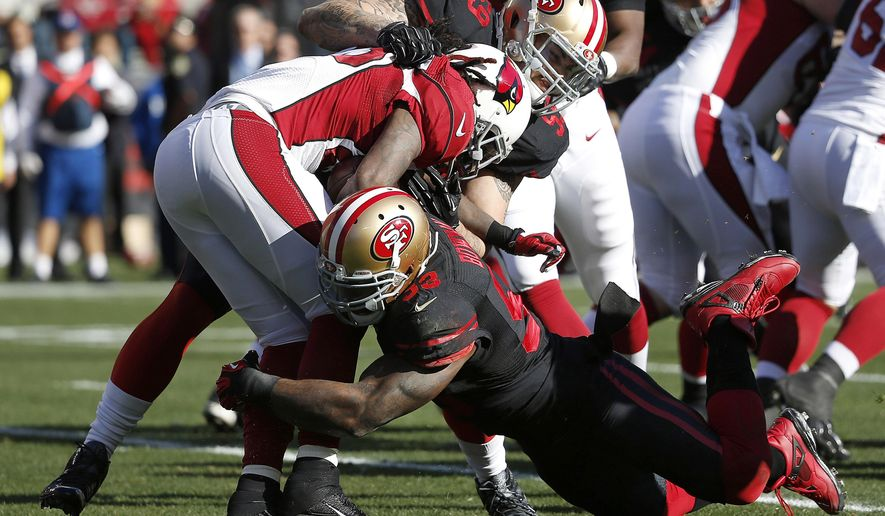 Arizona Cardinals running back Chris Johnson, center, is tackled by San Francisco 49ers linebacker Aaron Lynch (59) and linebacker NaVorro Bowman (53) during the first half of an NFL football game in Santa Clara, Calif., Sunday, Nov. 29, 2015. (AP Photo/Tony Avelar)