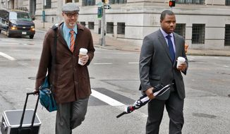 Baltimore City police officer William Porter, right, one of six Baltimore police officers charged with the death of Freddie Gray, walks to courthouse East with one of his attorneys on Wednesday, Dec. 2, 2015 in Baltimore.  Porter faces charges of involuntary manslaughter, second-degree assault, misconduct in office and reckless endangerment. The charges carry maximum prison terms totaling about 25 years. (Kevin Richardson/The Baltimore Sun via AP)