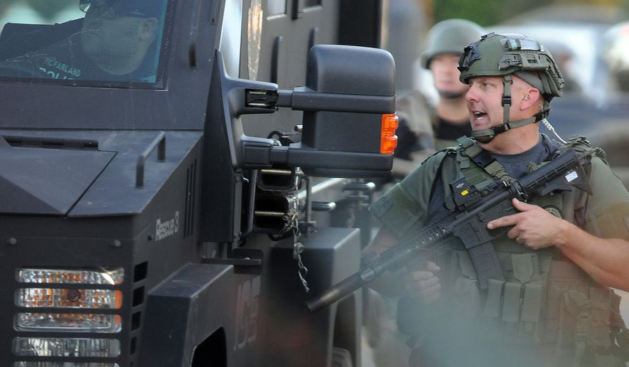 Authorities prepare to search an area near a church on Wednesday following a shooting that killed multiple people at a social services center for the disabled in San Bernardino, Calif. (The Victor Valley Daily Press via Associated Press)