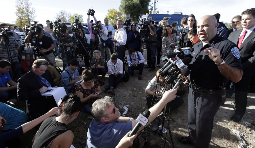 San Bernardino Police Chief Jarrod Burguan, right, talks to the media near the the site of a mass shooting on  Wednesday, Dec. 2, 2015, in San Bernardino, Calif. One or more gunmen opened fire Wednesday at a Southern California social services center, shooting several people as others locked themselves in their offices, desperately waiting to be rescued by police, witnesses and authorities said. Authorities said the shooting rampage killed multiple people and wounded others. (AP Photo/Chris Carlson)