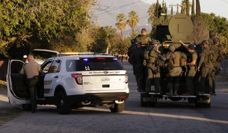 Law enforcement searches for a suspect in a mass shooting that occurred at a Southern California social services center on Wednesday in San Bernardino, Calif. (Associated Press)