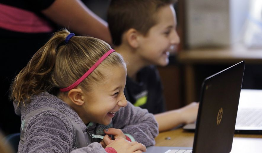 In this photo taken Nov. 4, 2015, fifth-grade students work on programming during their weekly computer science lesson at Marshall Elementary School in Marysville, Wash. The school, north of Seattle, joined a growing movement nationwide to expose more public school children to computer science, even as early as in kindergarten. (AP Photo/Elaine Thompson)