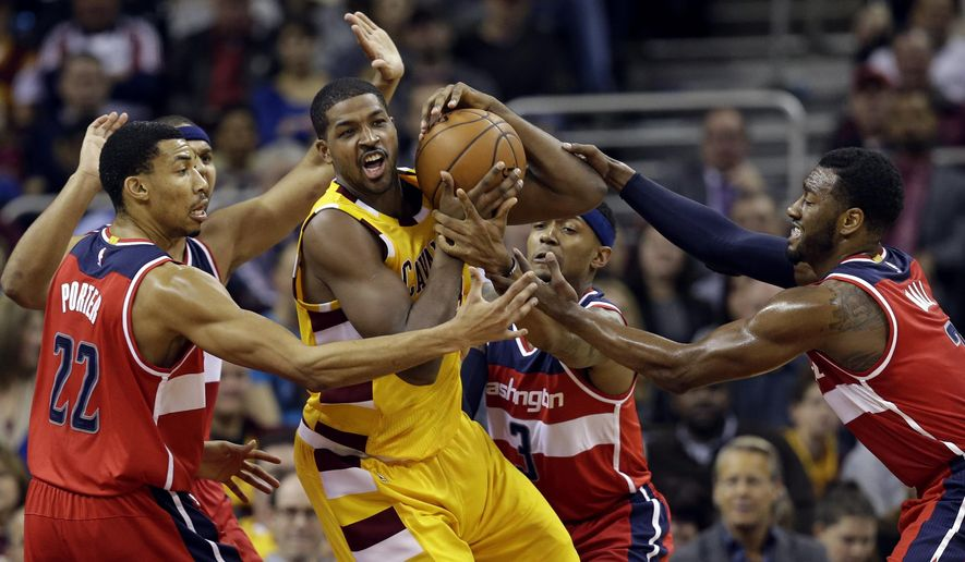 Cleveland Cavaliers' Tristan Thompson, center, tries to get past Washington Wizards' Otto Porter Jr., left to right, Jared Dudley, Bradley Beal and John Wall in the first half of an NBA basketball game Tuesday, Dec. 1, 2015, in Cleveland. (AP Photo/Tony Dejak)