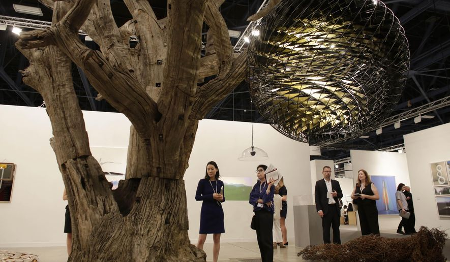 A tree sculpture by artist Ai Weiwei and a globe sculpture by artist Olafur Eliasson are displayed at Galerie neugerriemschneider, Wednesday, Dec. 2, 2015, at Art Basel Miami Beach, in Miami Beach, Fla. (AP Photo/Lynne Sladky)