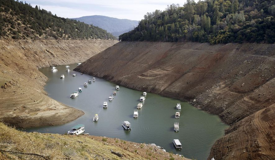 FILE - In this Thursday, Oct. 30, 2014, file photo, houseboats float in the drought-lowered waters of Oroville Lake near Oroville, Calif. On Tuesday, Dec. 1, 2015,the Department of Water Resources reported that Lake Oroville, the State Water Project's principal reservoir, is dipping toward its record low set in 1977. Public water agencies that serve millions of residents in drought-weary California might only receive 10 percent of expected supplies in 2016 _ half of the amount that flowed to them this year through the state's massive system of reservoirs and canals, state officials say. (AP Photo/Rich Pedroncelli, File)