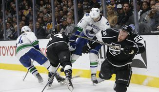Los Angeles Kings' Trevor Lewis, right, takes a tumble after colliding with Vancouver Canucks' Luca Sbisa, center right, of Italy, as Canucks' Matt Bartkowski, left, and Kings' Kyle Clifford fight for the puck during the second period of an NHL hockey game, Tuesday, Dec. 1, 2015, in Los Angeles. (AP Photo/Jae C. Hong)