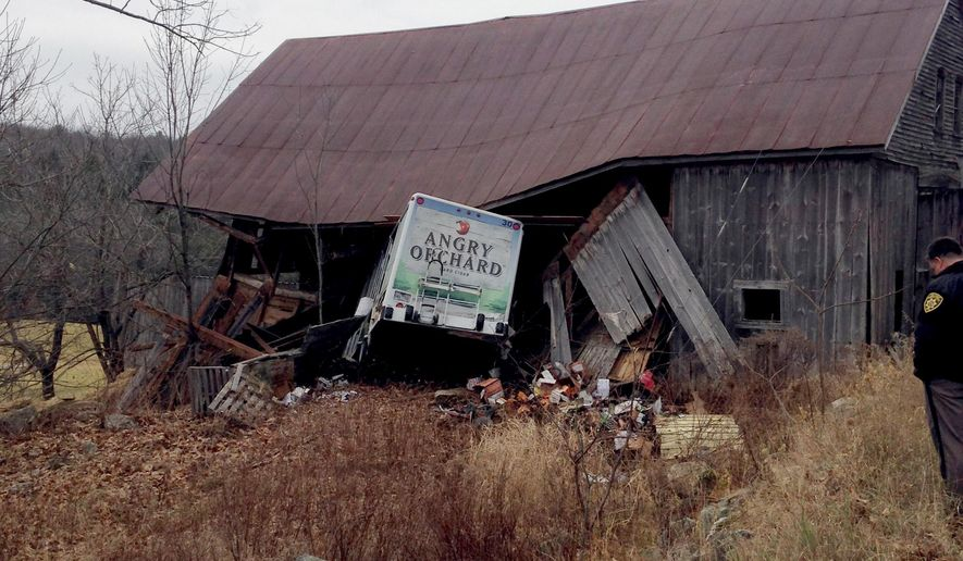 In this photo provided by the York County Sheriff's Office, authorities work at the scene where a hard-cider truck crashed into a barn following a high-speed police chase, Tuesday, Dec. 1, 2015, in Limerick, Maine. A woman is accused of stealing the truck in nearby Portland and leading police until the crash in Limerick. (Thomas Baran/York County Sheriff's Office via AP)