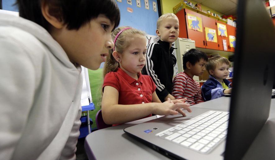 In this photo taken Nov. 4, 2015, kindergartner Lauren Meek, second left, works with a pair of second graders as they work on programming during their weekly computer science lesson at Marshall Elementary School in Marysville, Wash. The school, north of Seattle, joined a growing movement nationwide to expose more public school children to computer science, even as early as in kindergarten. Backed by technology leaders, nonprofits and companies, schools in New York, San Francisco and other cities have committed to offer computer science to students in all grade levels. (AP Photo/Elaine Thompson)