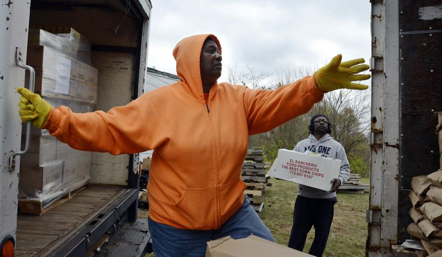 In this Nov. 6, 2015 photo, Lillian Spencer climbs into a truck to supervise the unloading of donated food at the Lord's Lambs Food Pantry in Hopkins Park, Ill. Spencer and her husband, Bruce, provide food to more than 1,500 people per month.  (Mike Voss/The Daily Journal via AP)