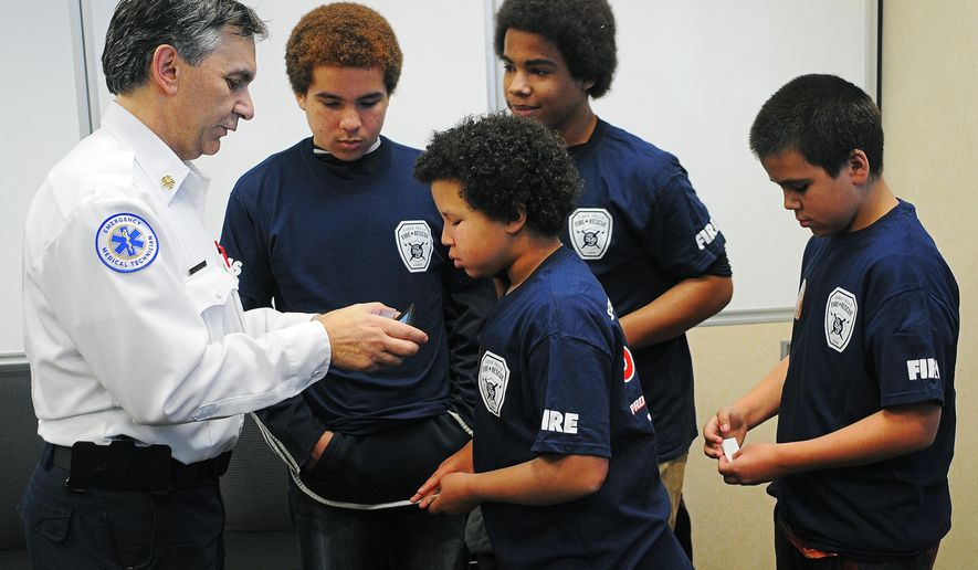 In this Monday, Dec. 1, 2015 photo, Chief Jim Sideras, with Sioux Falls Fire Rescue, shows, from left, Zavion Holloway, 13, Mystik Holloway, 10, Xaiveor Holloway, 15, and Dymond Holloway, 11, a group photo that he took after a news conference at the Law Enforcement Center in Sioux Falls, S.D. The Holloway children and their parents, Marchelle and Michael, were almost killed by carbon monoxide in their home over the weekend and were rescued by officer Ryan Chase, with the Sioux Falls Police Department. (Joe Ahlquist/Argus Leader via AP)