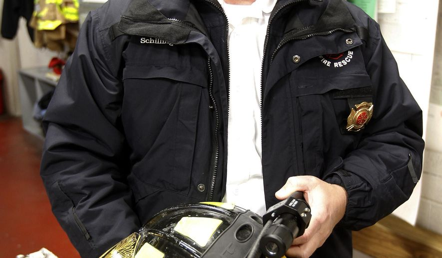 Cedar Falls' Fire Chief John Schilling holds a fire helmet explains the various uses the department could use the Fire Cams  Monday, Nov. 30, 2015, in Cedar Falls, Iowa. The fire department has purchased small cameras that can be attached to helmets, and plans to start using them next year. (Tiffany Rushing/The Courier via AP) MANDATORY CREDIT