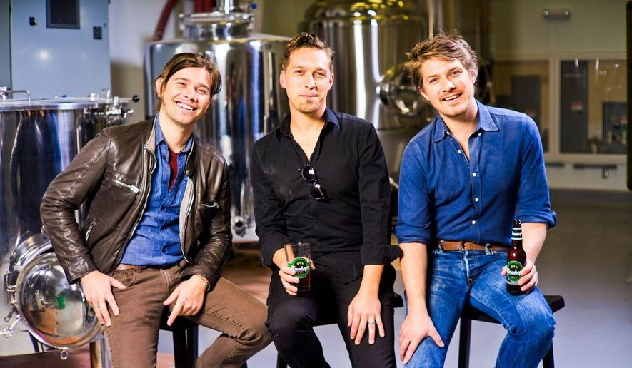 """In this photo taken on April 16, 2014, provided by Hanson Brothers Beer, from left to right, brothers Zac Hanson, Isaac Hanson and Taylor Hanson pose for a photo at Oklahoma City Brewing Company, in Oklahoma City. In 18 years the trio went from belting out """"MMMBop"""" to brewing their own Mmmhops beer. (Matthew Swaggart/Hanson Brothers Beer via AP)"""